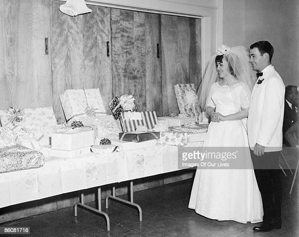 Happy newlyweds looking at wedding gifts on table