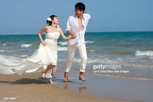 Happy Newlyweds Running on the beach