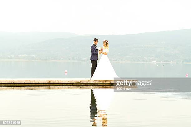 Happy newlyweds standing on pier
