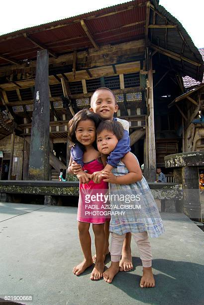 happy Nias kids posed in front of Chief's House of Bawamataluo