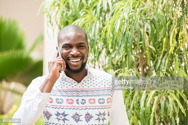 Happy Nigerian man on mobile phone smiling