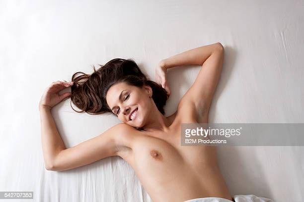 happy nude young woman laying in bed - image stockfoto's en -beelden