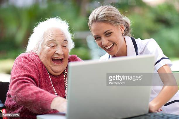 Happy nurse and senior woman using laptop together