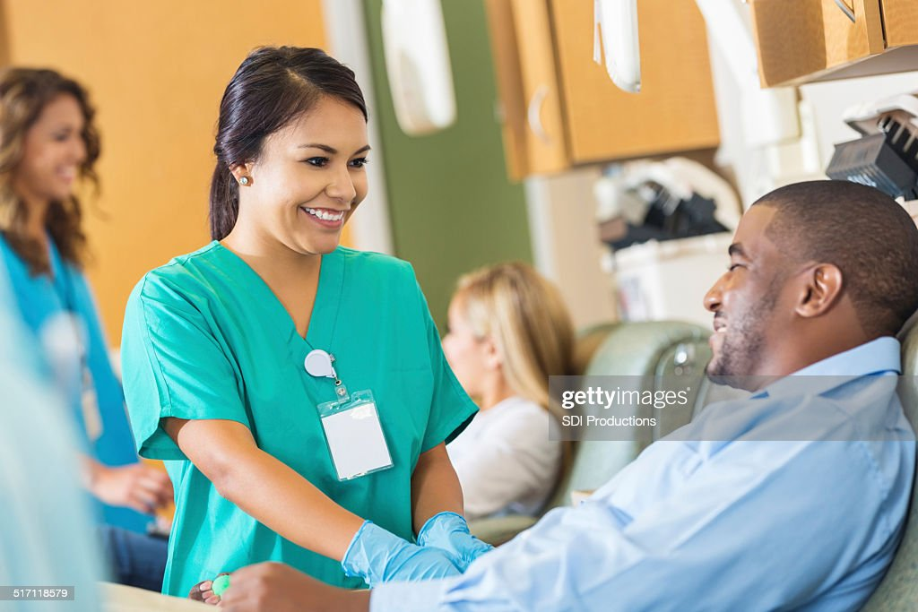 Happy nurse comforting patient while he donates blood to hospital : Stock Photo