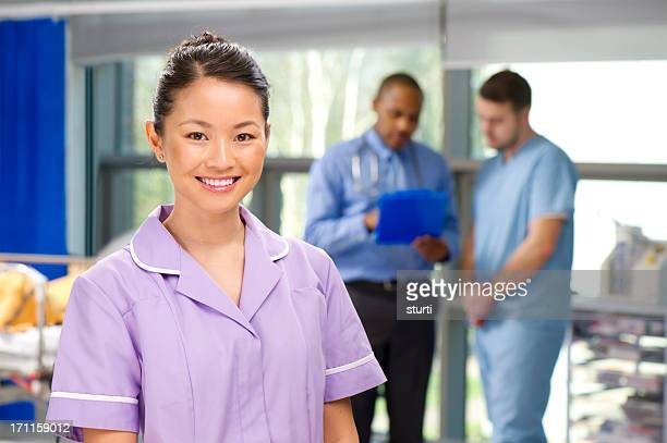 happy nurse on a busy ward - nursing assistant stock pictures, royalty-free photos & images