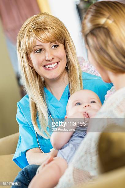 Happy nurse or lactation consultant talking to new mothers