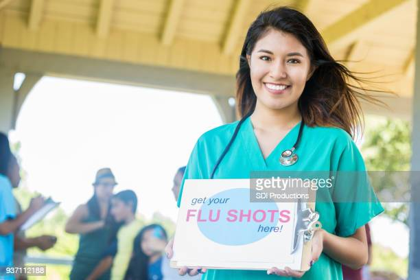 happy nurse promotes free flu shots - flu shot stock photos and pictures