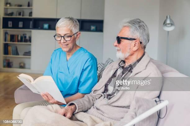 視覚障害者の患者に読んでハッピー ナース - 白杖 ストックフォトと画像