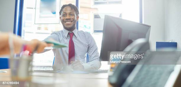 happy office worker passing files - real estate office stock photos and pictures