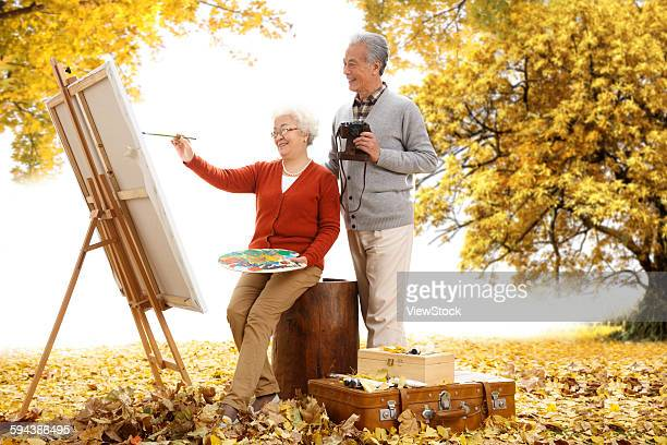 Happy old couple in the outdoor painting