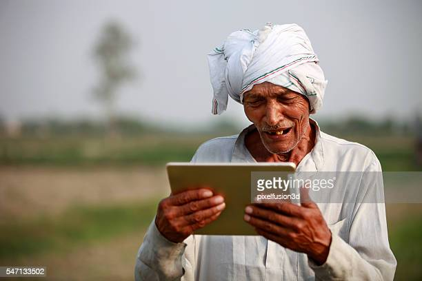 Happy  Old farmer holding digital tablet