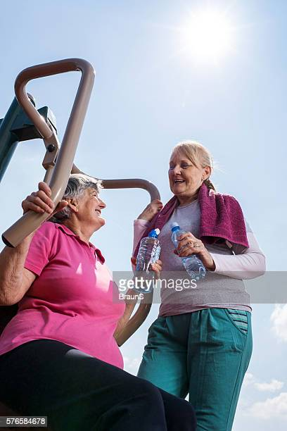Happy old friends talking to each other at outdoor gym.