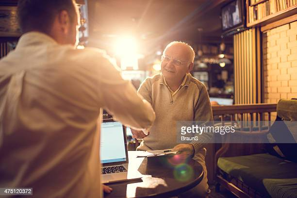 Happy old man come to an agreement with insurance agent.