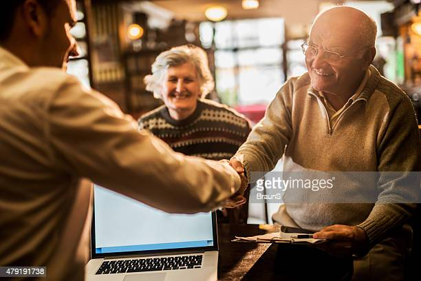Happy old people come to an agreement with insurance agent.