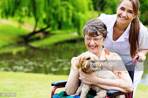 Happy old wheelchair-bound woman with pet dog and smiling caregiver