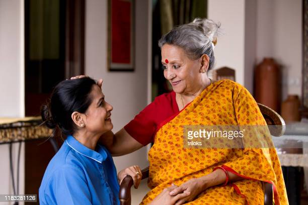 happy old woman giving blessings to female nurse at home - religious blessing stock pictures, royalty-free photos & images