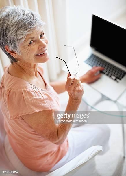 Vieille femme heureuse avec ordinateur portable vous donner le sourire.