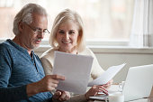 Happy older aged couple holding reading good news in document