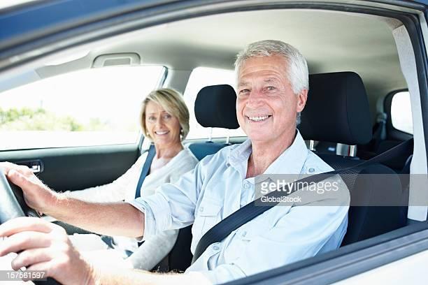 Feliz pareja de ancianos en automóvil