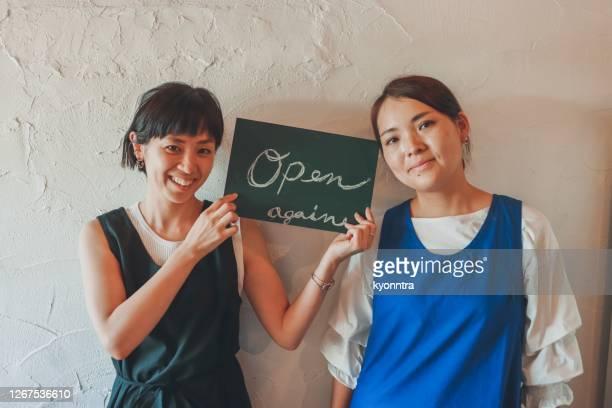 カフェで看板を掲げ幸せなオーナー - 非常事態宣言 ストックフォトと画像