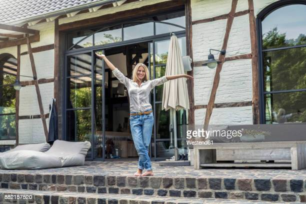 Happy owner standing in front of her country house