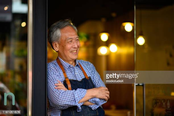 happy owner with arms crossed at restaurant - contemplation outside stock pictures, royalty-free photos & images