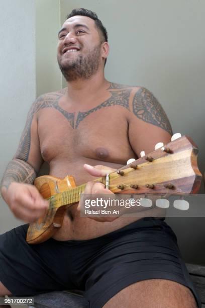 "happy pacific islander man plays music on ukulele""nguitar - rafael ben ari stock-fotos und bilder"