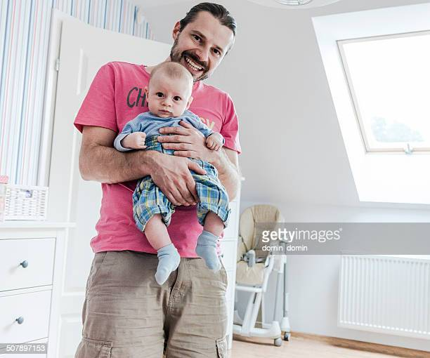 Happy parenting, single father with baby on hands, home interior