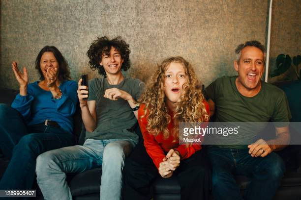 happy parents and children cheering while watching sports in living room at night - television stock pictures, royalty-free photos & images
