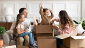 Happy parents and children playing on moving day unpacking boxes