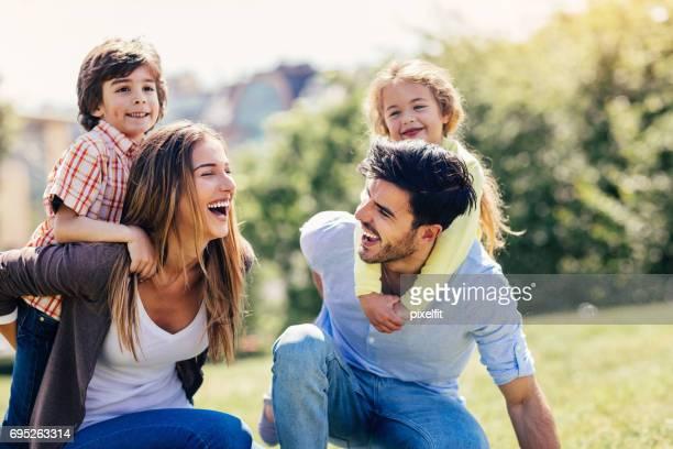Glückliche Eltern und Kinder spielen im freien