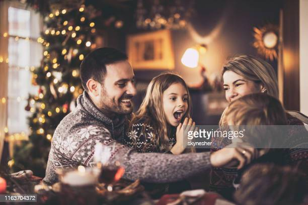 happy parents and their kids having fun during new year's day in dining room. - new year's day stock pictures, royalty-free photos & images