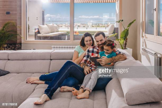 happy parents and their small daughter using touchpad in the living room. - penthouse girl stock photos and pictures