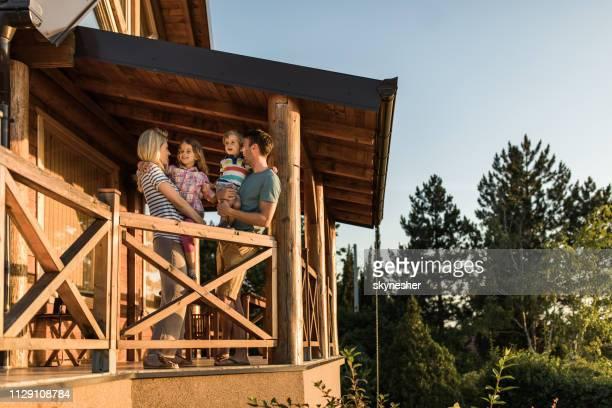 heureux parents et leurs petits enfants parler sur un balcon de leur chalet. - chalet de montagne photos et images de collection