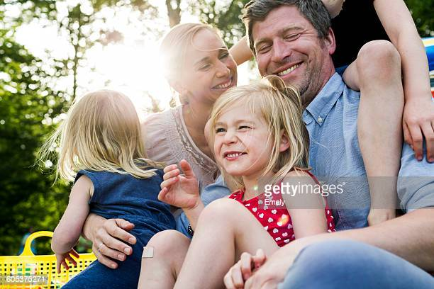 happy parents and three daughters sharing family picnic in park - picknick stock-fotos und bilder