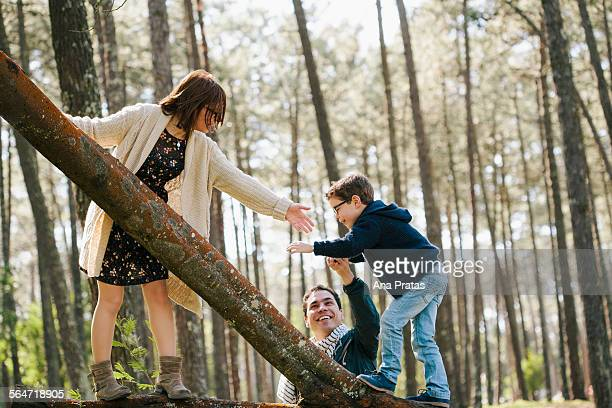 Happy parents assisting son in climbing tree at forest