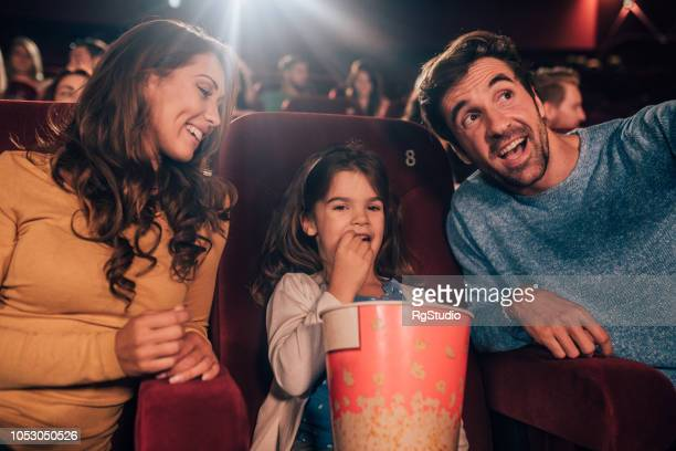 Happy parents at cinema with a daughter