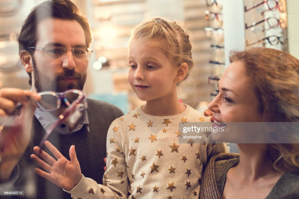 Happy parents choosing eyeglasses for their small daughter at optician store. : Stock Photo