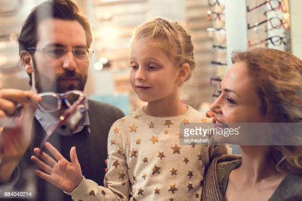 Happy parents choosing eyeglasses for their small daughter at optician store.
