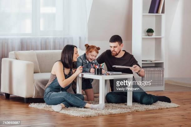 Happy parents drawing with daughter in living room at home