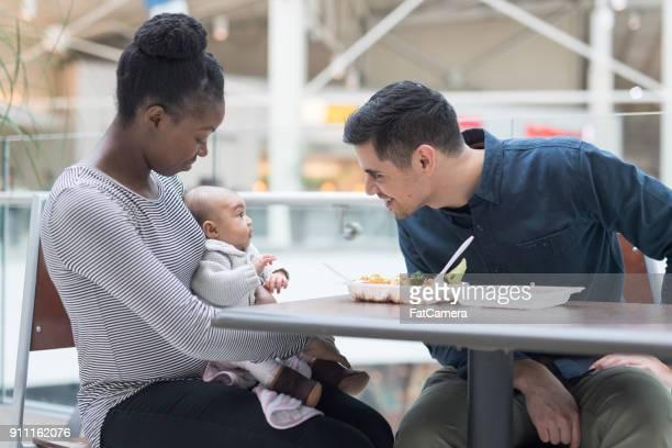 幸せな親を彼らの赤ちゃんと昼食を食べ