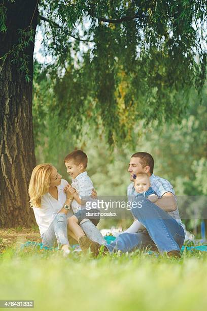Happy parents enjoying summer with their kids by the river