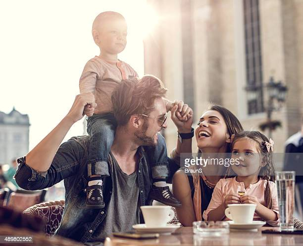 Happy parents having fun with their children in a cafe.