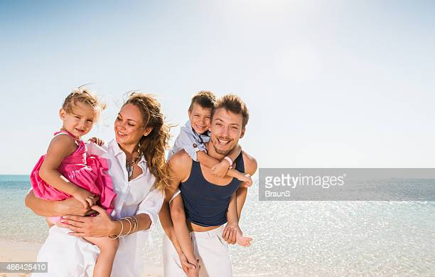 Happy parents having fun with their children on the beach.