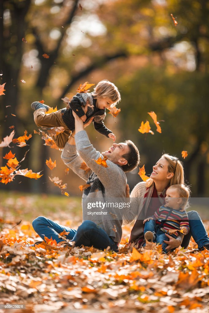 Happy parents having fun with their small children in autumn day. : Stock Photo