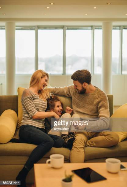 Happy parents having fun with their small daughter on sofa at home.