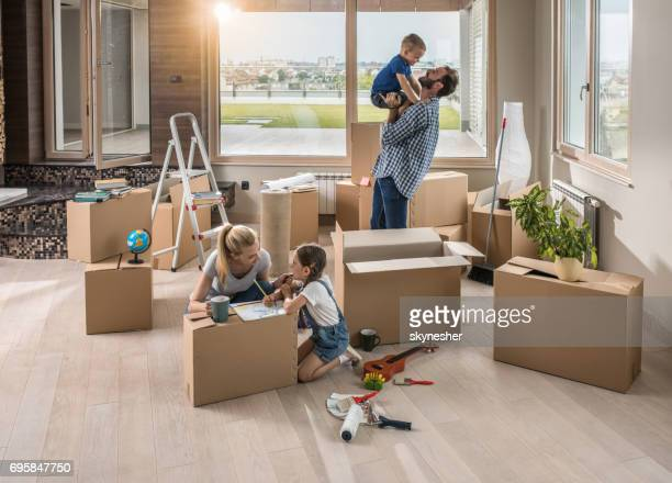 happy parents having fun with their small kids in their new apartment. - penthouse girls stock pictures, royalty-free photos & images