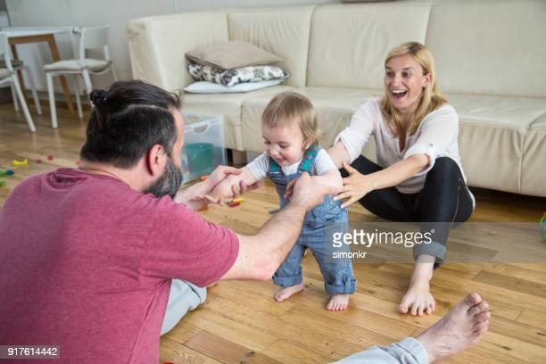 Happy parents helping little son walking in living room
