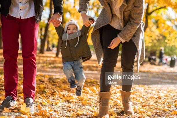 gelukkige ouders hand in hand met hun kleine zoon die is springen in de natuur. - sociale dienst stockfoto's en -beelden