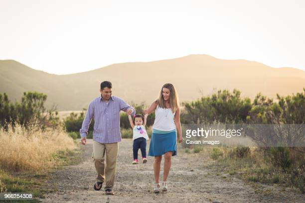 happy parents lifting daughter while walking on field against clear sky - femme entre deux hommes photos et images de collection